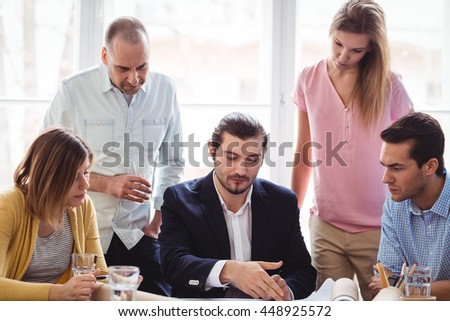 Businessman discussing with coworkers in meeting room - stock photo