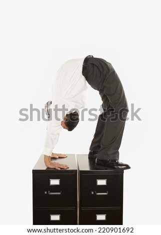 Businessman doing a back bend on filing cabinet - stock photo