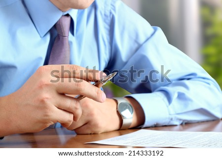businessman  doing business, sitting at his desk in the office, analyzing  data in  documents - stock photo