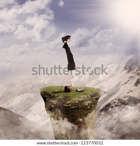 Businessman doing handstand in front of his laptop by nature - stock photo