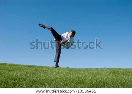 Businessman doing karate moves on green grass