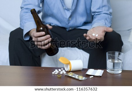 Businessman doing mixed use of drugs and alcohol. - stock photo