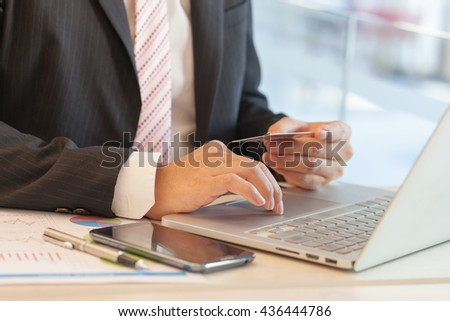 Businessman doing online banking, making a payment or purchasing goods on the internet entering his credit card details on a laptop, close up view of his hands - stock photo