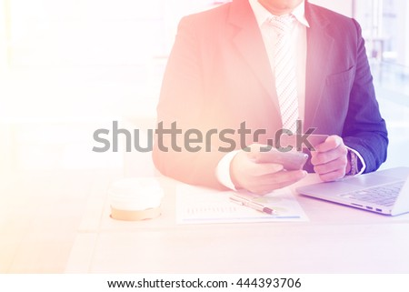 Businessman doing online banking making a payment or purchasing on the internet entering his credit card details on a laptop - stock photo
