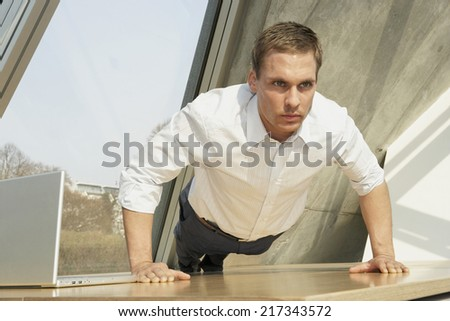 Businessman doing push-ups in the office - stock photo