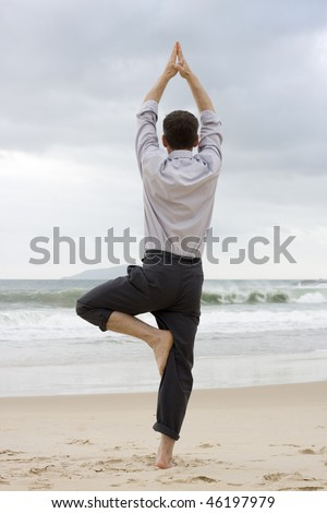 Businessman doing relaxation exercises on a beach - stock photo