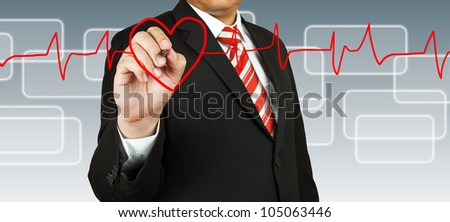 Businessman draw a pulse line with heart - stock photo