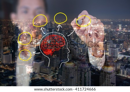 Businessman drawing a brian on cityscape background - stock photo