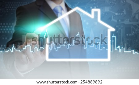 Businessman drawing a house with her finger on a tactile screen  - stock photo