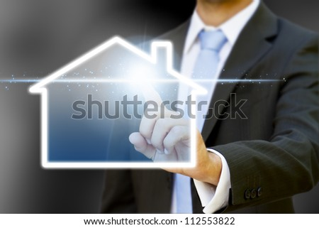 Businessman drawing a house with his finger - stock photo