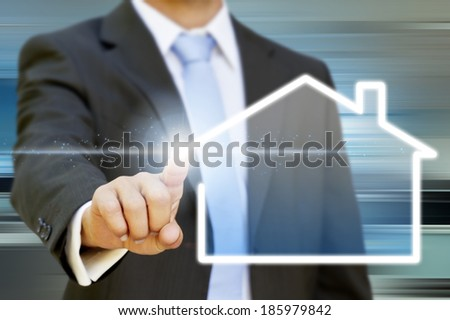 Businessman drawing a house with his finger on a tactile screen