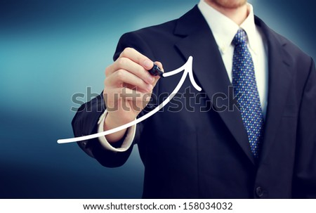 Businessman drawing a rising arrow over blue background - stock photo