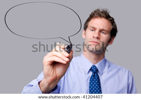 Businessman drawing a speech bubble on a glass screen, add your own text. The background is a uniform color all over so you can increase the copy space easily. Focus is on his hand and pen.