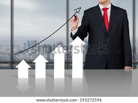 Businessman drawing an arrow chart.