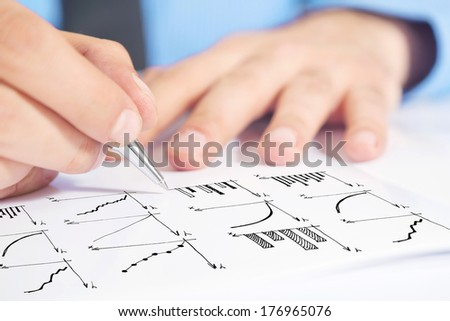 Businessman drawing bar chart and other infographics in note pad. Close up image with selective focus. Business situation. - stock photo