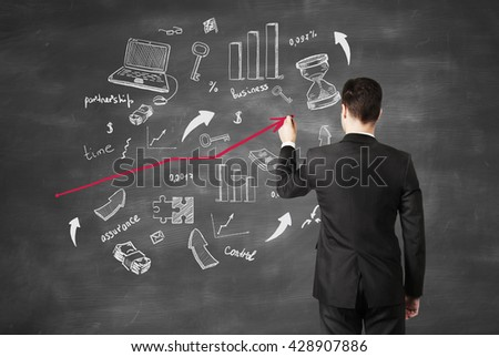 businessman drawing business icons on chalk board - stock photo