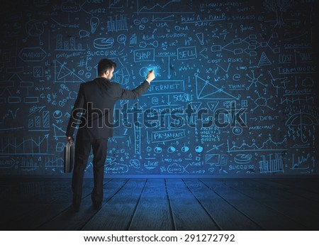 Businessman drawing business schemes on glass wall - stock photo