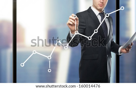 businessman drawing chart on city background - stock photo
