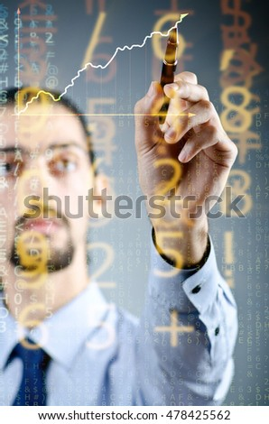 Businessman drawing charts among numbers
