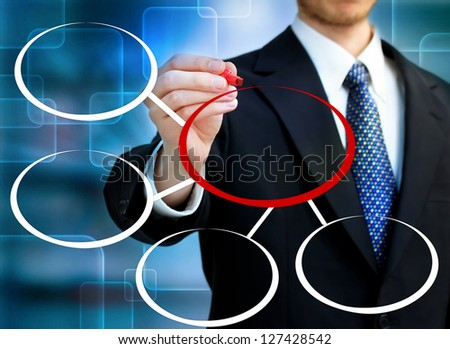 Businessman drawing circles in blue technology background - stock photo