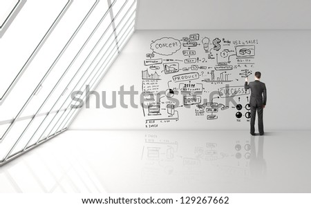 businessman drawing concept in big office - stock photo