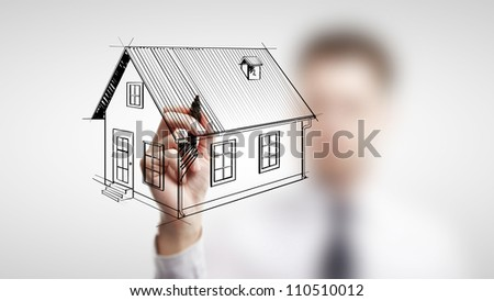 businessman drawing cottage on a white background - stock photo