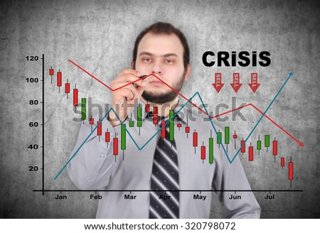 businessman drawing crisis chart on a gray wall background - stock photo