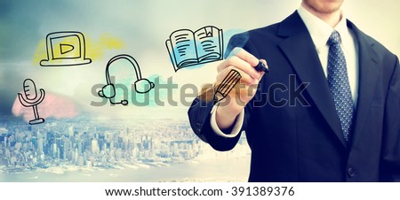 Businessman drawing E-learning concept on blurred abstract background  - stock photo