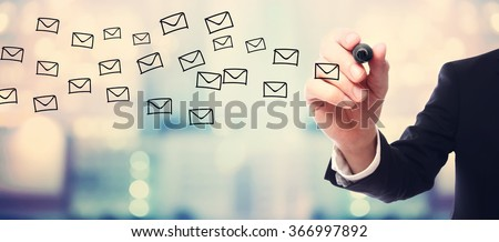 Businessman drawing E-mails concept on blurred abstract background  - stock photo