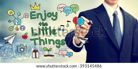 Businessman drawing Enjoy the Little Things concept above the city - stock photo
