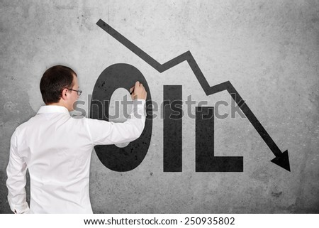 businessman drawing falling oil chart on concrete wall - stock photo