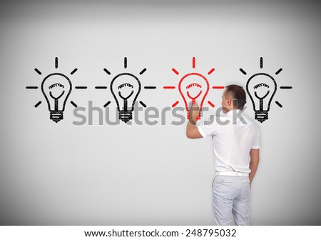 businessman drawing four lamps on concrete wall - stock photo