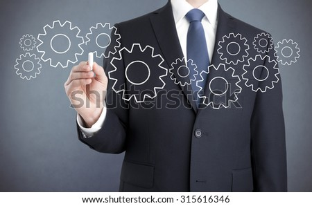 Businessman drawing gears with chalk  - stock photo