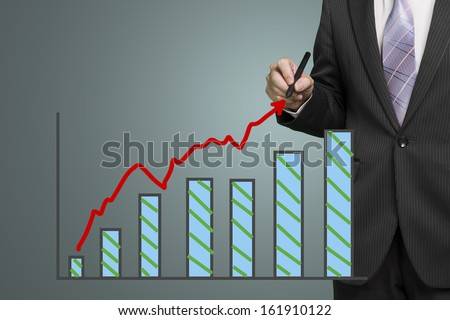 Businessman drawing growth red arrow and chart in dark background  - stock photo