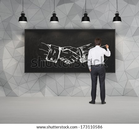 Businessman drawing handshake in a chalkboard 2 - stock photo