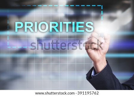 "Businessman drawing on virtual screen ""Priorities"". - stock photo"