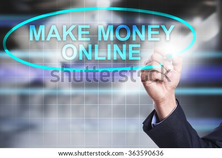 """Businessman drawing on virtual screen text """"Make money online"""". Business concept. Internet concept. - stock photo"""