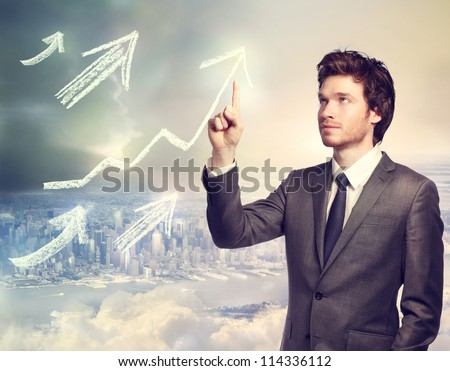 Businessman drawing rising arrows on top of the city - stock photo