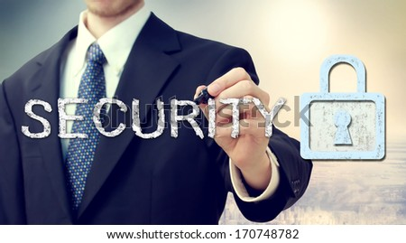 Businessman drawing security text and key lock concept  - stock photo