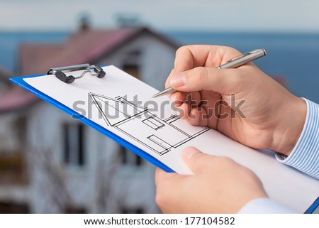 Businessman draws a drawing of a house on a piece of paper on the background of an apartment building  - stock photo