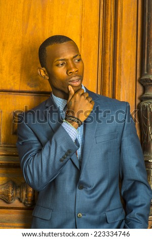 Businessman. Dressing formally in blue suit, patterned undershirt, short haircut, wooden bracelets, a hand touching his chin, a young guy standing in the front of an old style office door, thinking. - stock photo