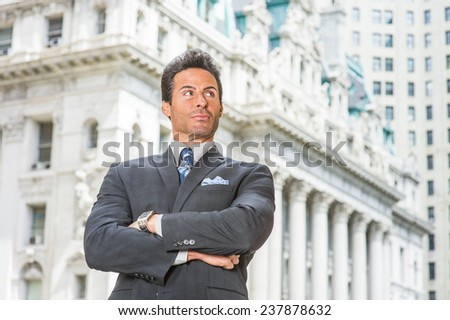 Businessman. Dressing in dark blue suit, necktie, wristwatch, crossing arms, a handsome, sexy, middle age businessman is standing in the front of an office building, confidently looking forward. - stock photo
