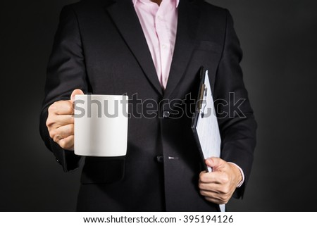 Businessman drinking coffee and holding work document - stock photo