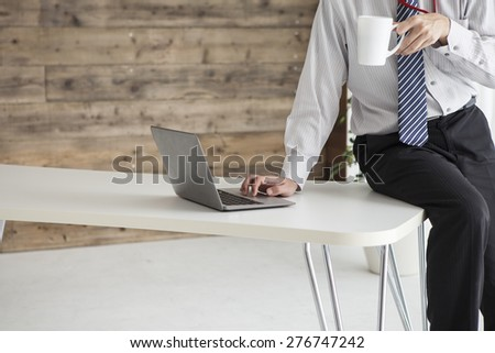 Businessman drinking coffee and reading news  - stock photo