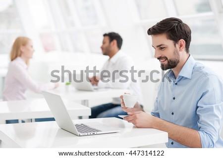 Businessman drinking coffee while working