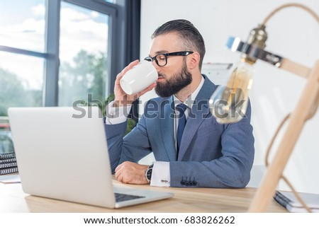 businessman drinking coffee while working at workplace with laptop in office