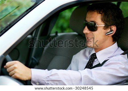 Businessman driving in the car with blue-tooth, handsfree