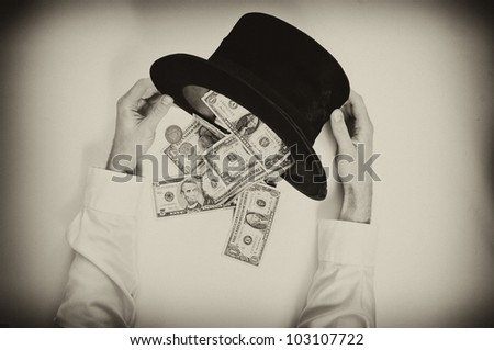 Businessman dumps the money from an old black hat. Vintage style image - stock photo