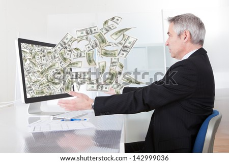 Businessman Earning Lots Of Cash In Internet - stock photo