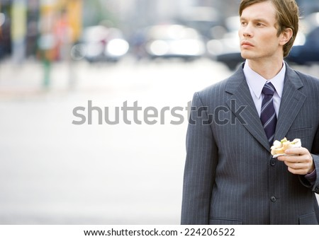 Businessman eating on the go - stock photo